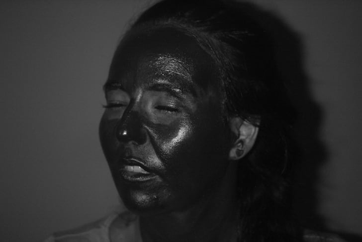 A woman turns her face to show sunscreen coverage in a UV image.