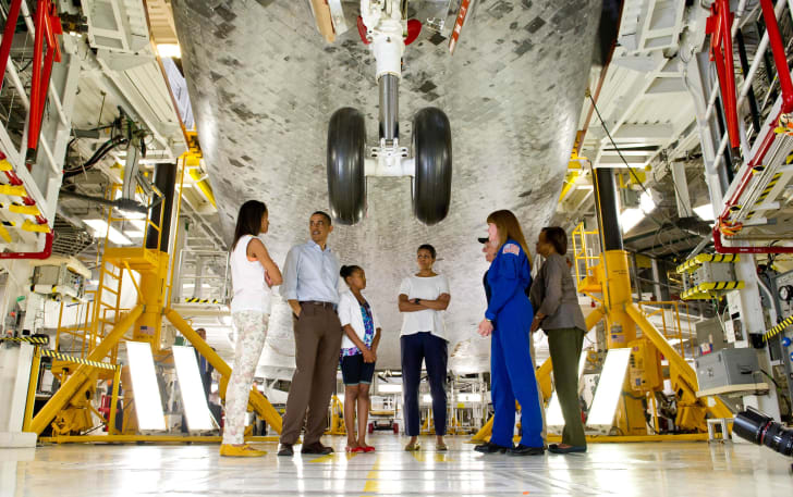 President Obama and the First Family stand beneath the Space Shuttle Atlantis prior to its final flight.