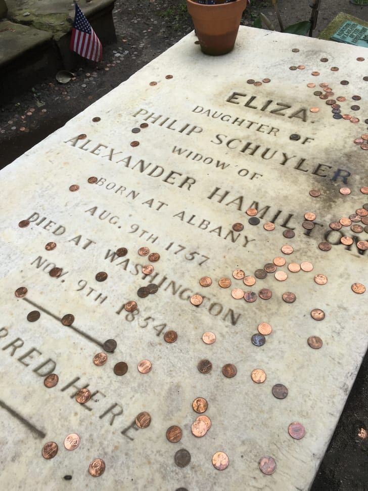 The flat, rectangular white marble gravestone of Eliza Hamilton, inscribed with her name, relationships, birthday and deathday. Pennies have been strewn across the stone.