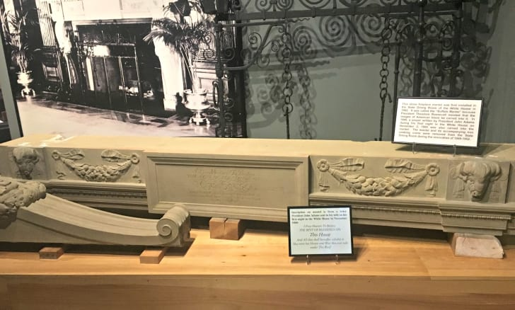 A large stone fireplace mantel with intricate buffalo carvings, on display on top of a large wooden block. A black and white photo of the mantel in its original setting at the White House sits behind the piece.