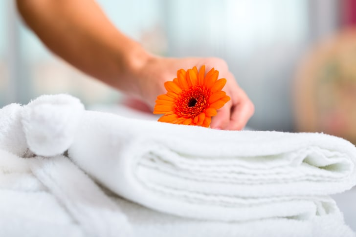A maid putting an orange daisy on hotel towels