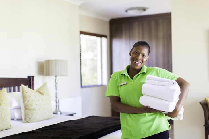 Smiling maid in a hotel room