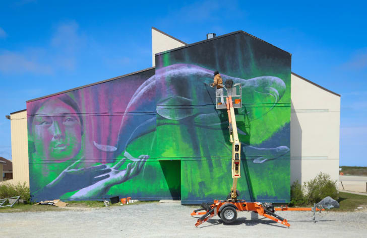 Artist painting a polar bear mural on the side of a building.