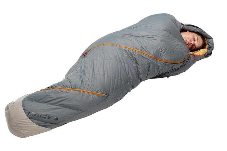 A man sleeps in a brown Kelty sleeping bag.
