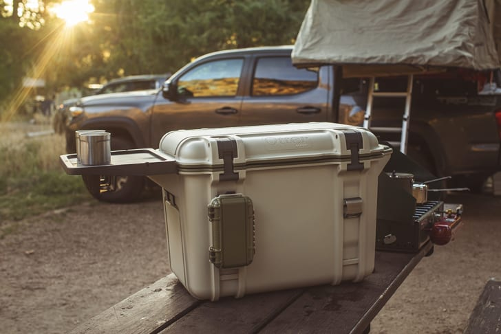 An Otterbox cooler with a side table sits on a picnic table in front of a truck.