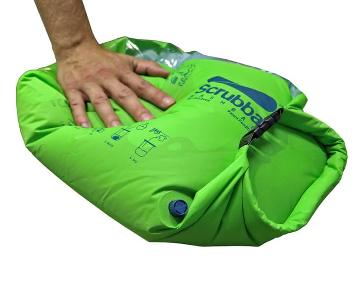 A man's hand rubs a Scrubba bag filled with water and clothes.