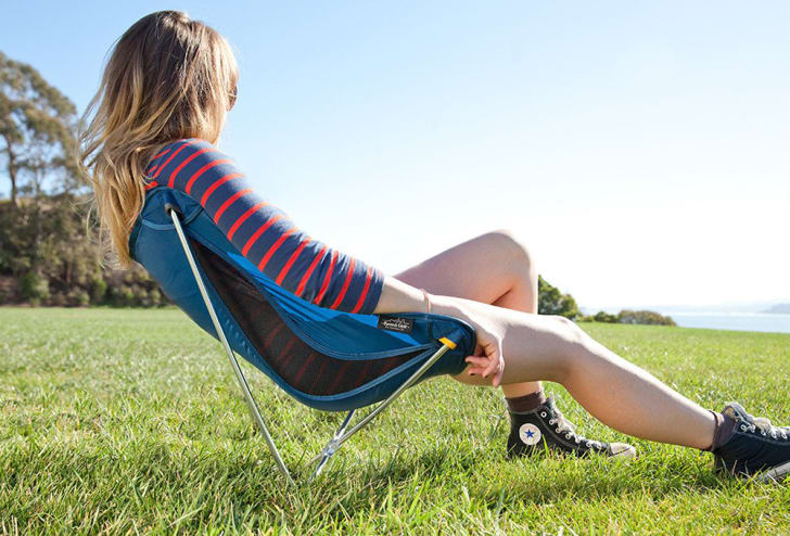 A blonde woman relaxes in the grass in a Monarch chair.