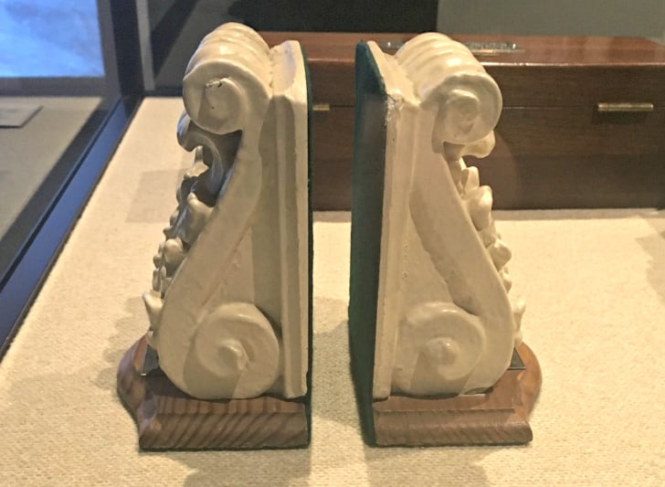 Two pieces of architectural scrollwork, painted white and mounted on wooden pieces to create bookends.