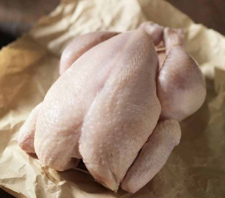 A raw, whole chicken on butcher paper