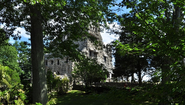 The exterior of Gillette castle, partially hidden by trees