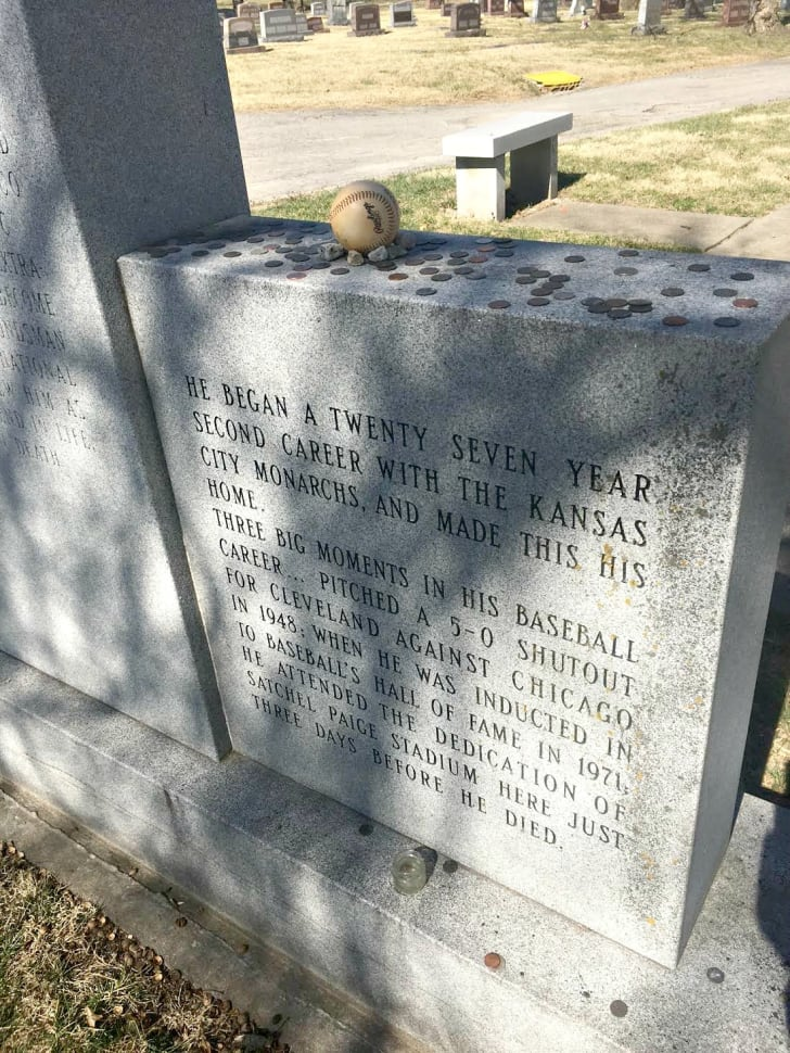 Part of the gravestone of baseball legend Satchel Paige and his wife, which provides the highlights of his career. The top of the grave is dotted with baseballs and coins.