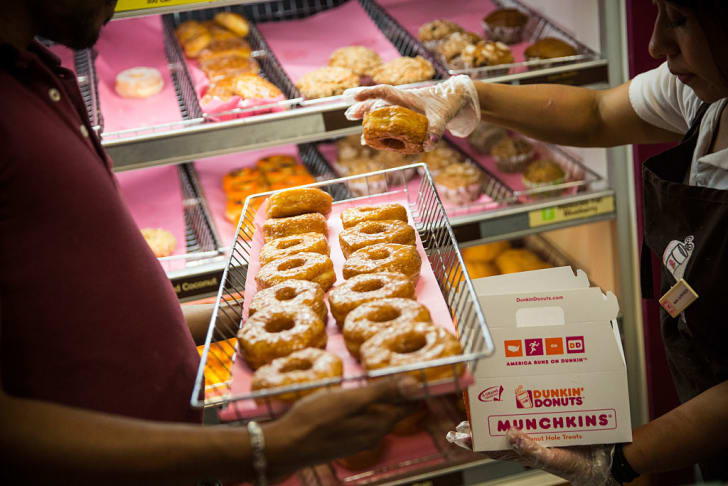 Dunkin' Donuts employee places a 'croissant doughnut' in a box