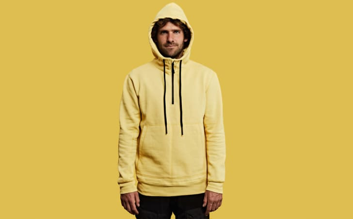 Man wearing yellow hoodie standing against yellow background.