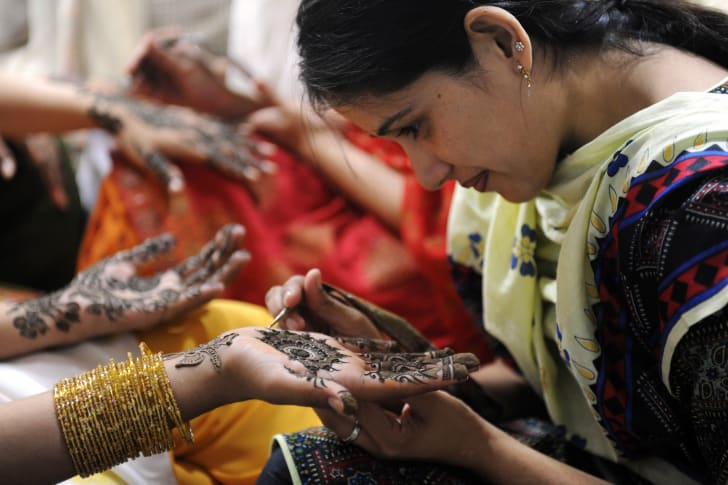 A Pakistani beautician applies henna on a customer's hand at a beauty salon in Karachi ahead of the forthcoming Eid al-Fitr festival.
