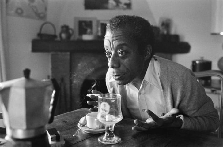 James Baldwin smokes a cigarette at home