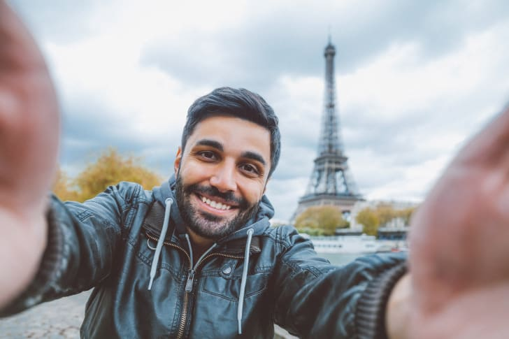 Man takes a selfie with the Eiffel Tower.