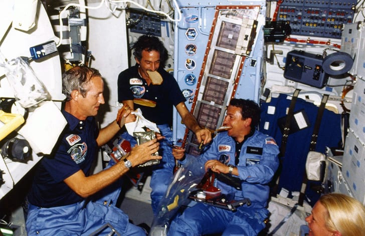 Astronauts eat bread slices on the space shuttle Discovery.