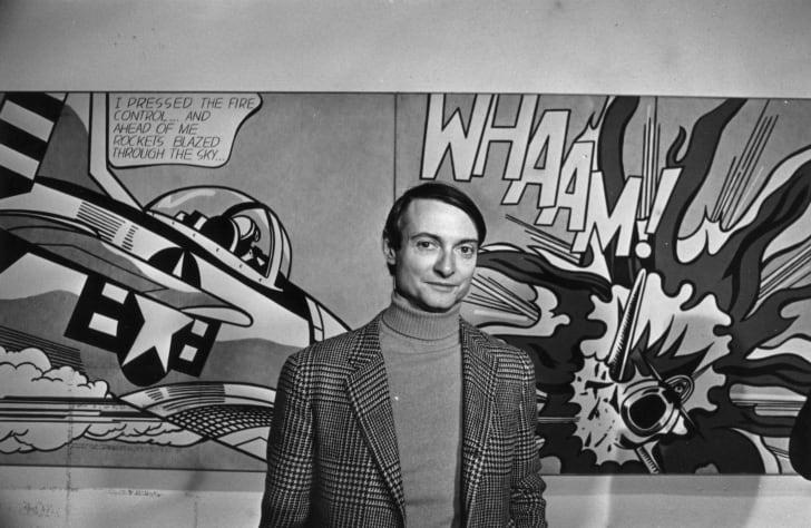 American pop artist Roy Lichtenstein stands in front of art