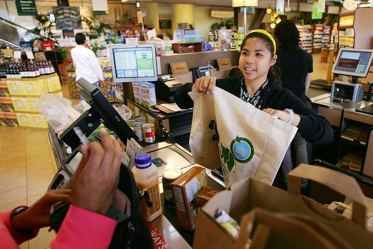 Cashier hands out free reusable grocery bags at whole foods