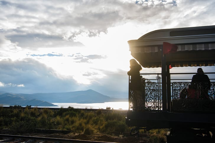 A woman looks out over the rail of the train's observatory car toward a sunset over a lake.