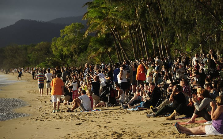 spectators on the beach for a total solar eclipse in Palm Cove, Australia
