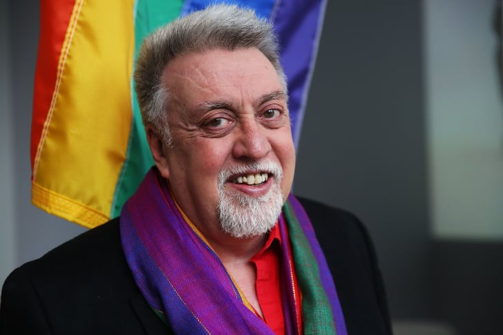 Artist Gilbert Baker poses with the rainbow flag, which he designed.