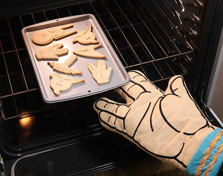 Pulling a pan from the oven with a Spock oven mitt.
