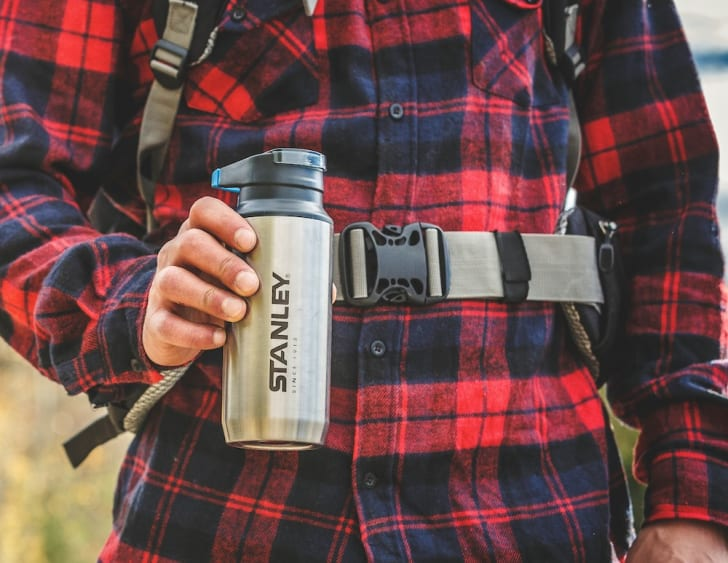Man in flannel holding travel mug.