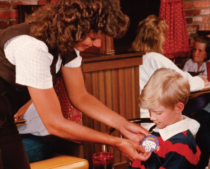 Inside a Pizza Hut restaurant, a woman pins a blue Book It button on a boy's shirt. Based on the hairstyles and clothing, the photo dates from the mid 1980s.