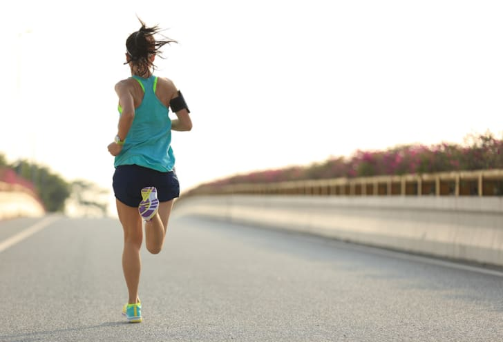 A woman running outside, seen from behind