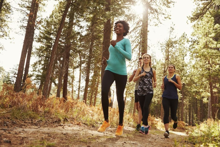 A group of people jogging in the woods