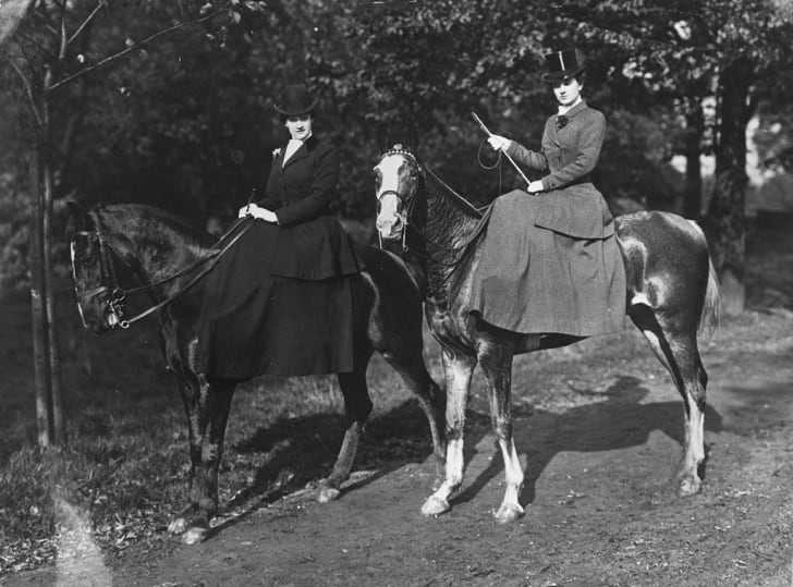 Two ladies pose in riding habits