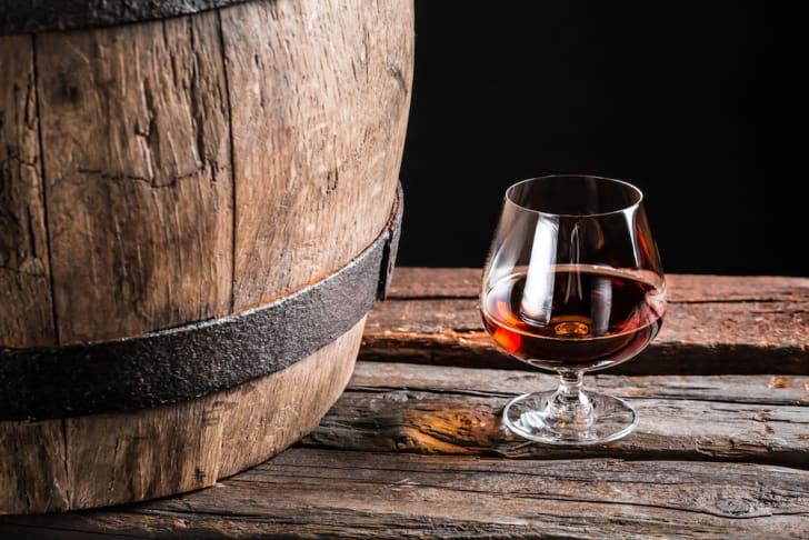 A glass of cognac next to an oak barrel