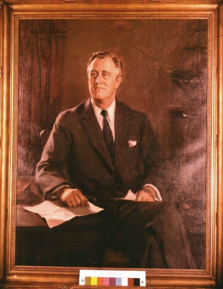 An oil painting of American President Franklin Delano Roosevelt, wearing a suit and seated with his legs crossed. One hand rests on top of a piece of paper on a desk and the other holds a piece of paper in his lap.