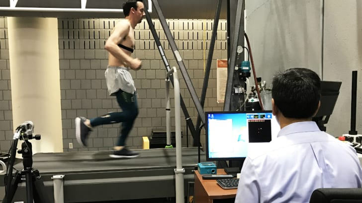 A man runs on a treadmill while a researcher monitors his progress and vital signs on a screen.