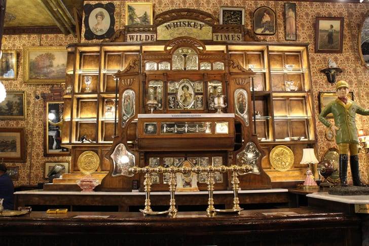 """A view of the large wooden bar that reads """"Wilde Whiskey Times"""" above"""
