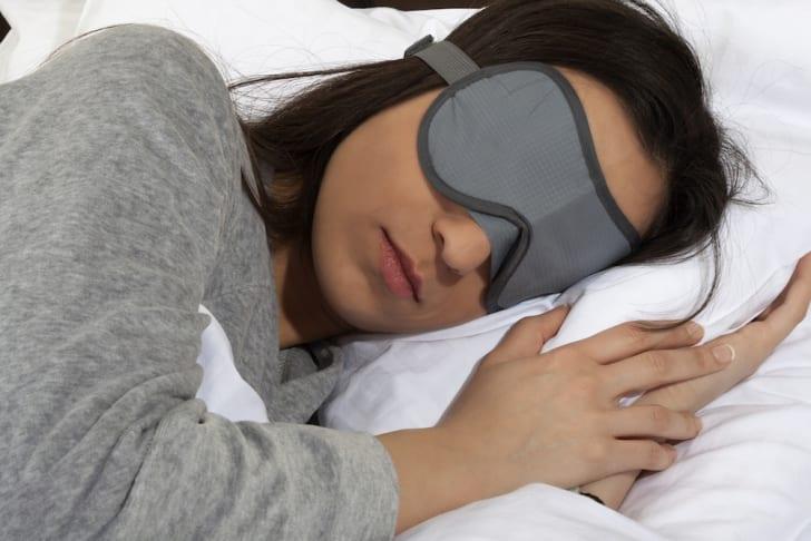 Woman sleeping while wearing an eye mask