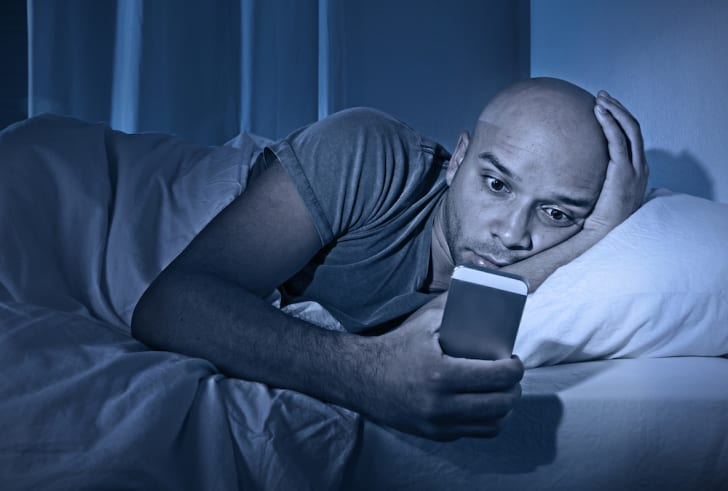 Man looking at his cell phone while in bed