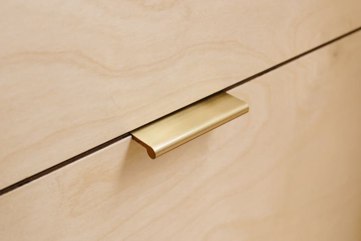 Plykea kitchen cabinet with brass handle.