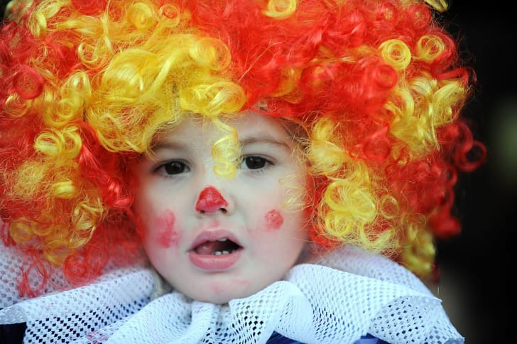A young audience member is dressed as a clown