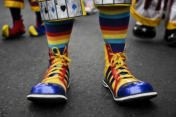 A clown shows off a pair of oversized shoes