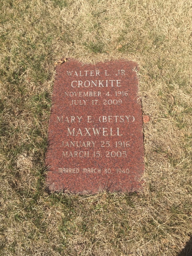 Close-up image of the gravestone of news anchor Walter Cronkite and his wife, Mary. The small stone is pink marble and set into the ground.