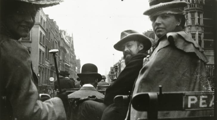 A black and white photo of passengers on an old-fashioned bus.