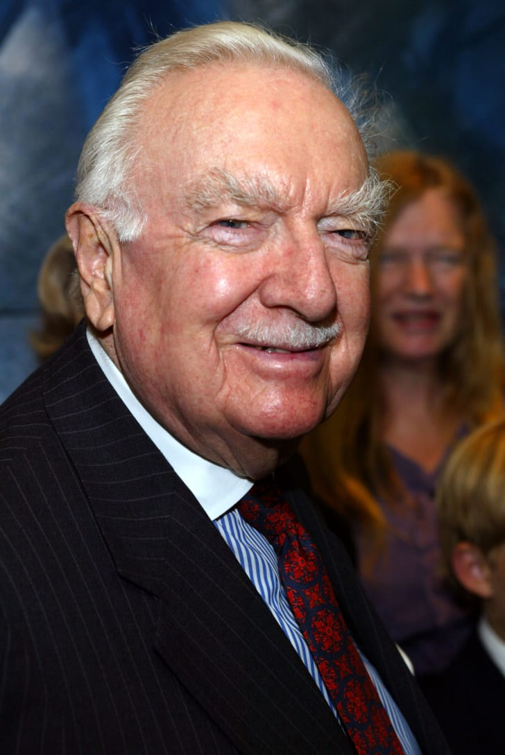 Color photo of anchorman Walter Cronkite in his later years, wearing a pinstriped suit, a blue-and-white-striped dress shirt, and a navy tie with a red pattern on it.
