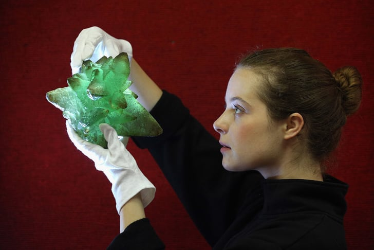 An employee at Bonhams auction house holds a 'Kryptonite' prop crystal from the film 'Superman III',