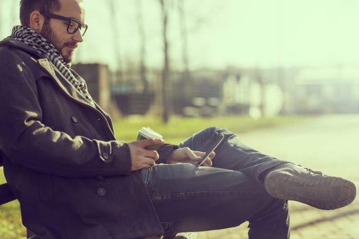 A man sitting on a park bench reading on his smartphone
