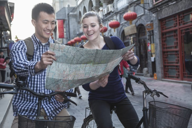 Man in woman with bicycles read a map in an Asian city