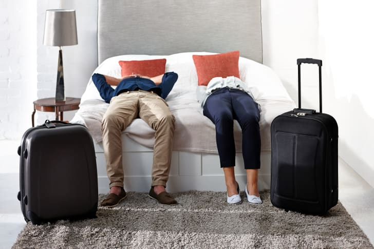 Exhausted couple lying on a bed with luggage by their feet