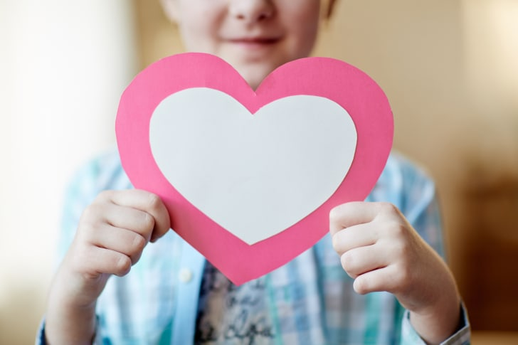 child holding cut-out heart