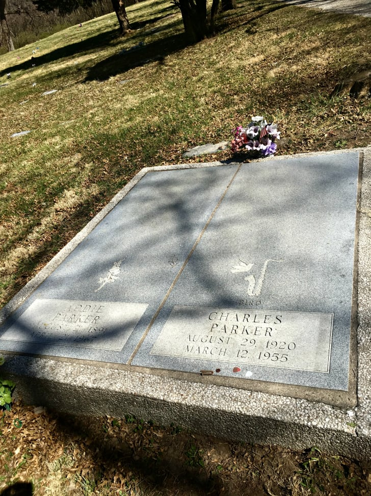 Gravestone of jazz musician Charlie Parker and his mother, Addie Parker, including birth dates, death dates, and an engraving of a bird and a saxophone.